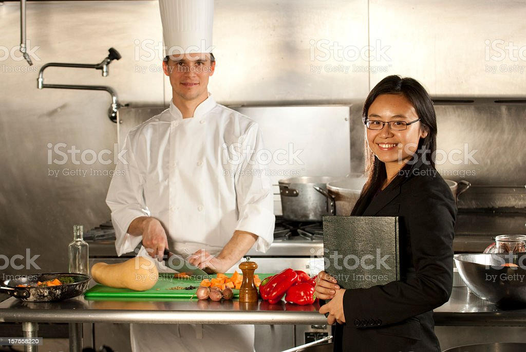 A chef and a waitress in the kitchen royalty-free stock photo