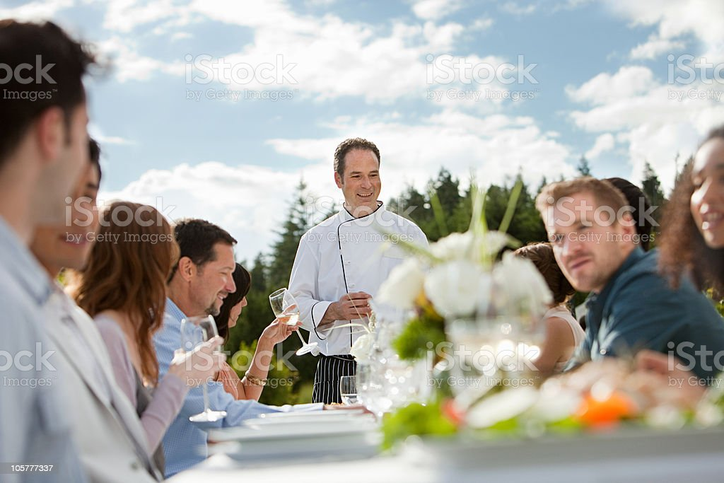 Chef and people at outdoor dinner party stock photo