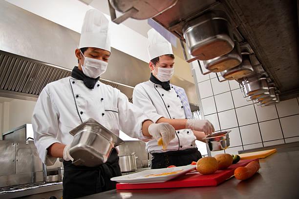 Chefkoch und Auszubildender in einem hotel in der Küche, die Zubereitung einer Mahlzeit – Foto