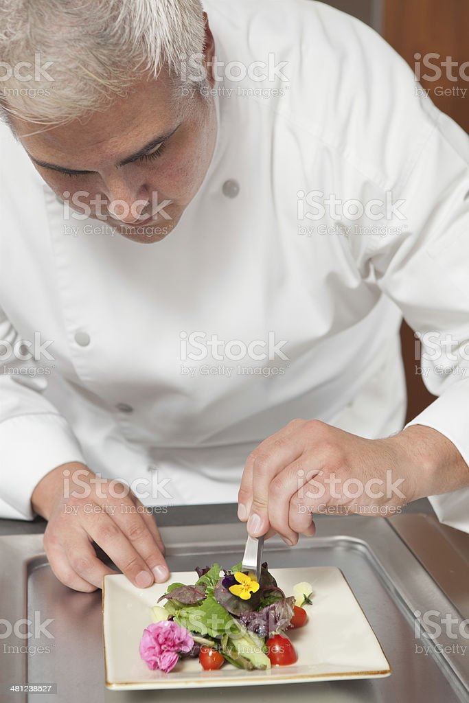 Chef Arranging Edible Flowers On Salad stock photo