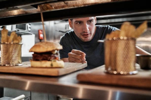 Chef arrangiert vorbereitete Bestellung auf Küchentheke – Foto