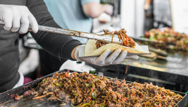 Chef at a street food market preparing a taco Cooking a taco at a street food market food festival stock pictures, royalty-free photos & images