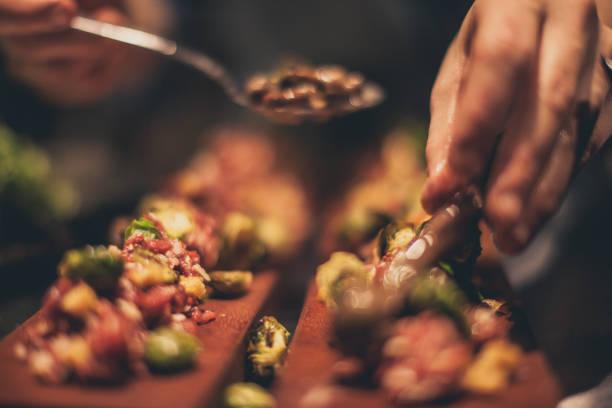 koch bei der arbeit. kochen in der großküche caterer - tapas stock-fotos und bilder