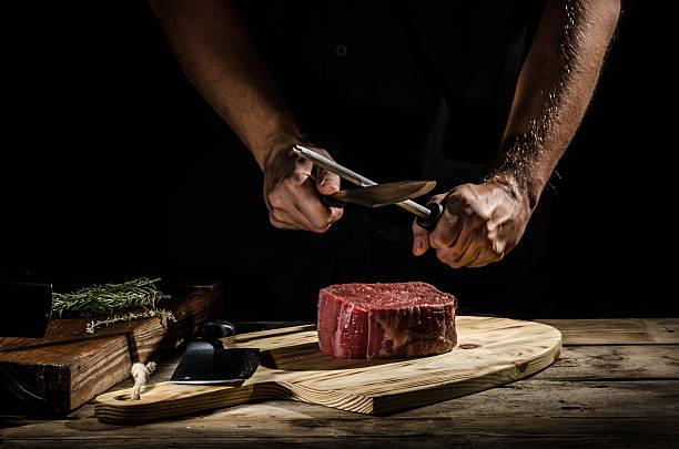 Chef butcher prepare beef steak - foto de stock