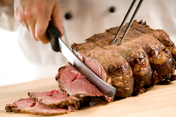Chef carving perfectly cooked prime rib roast beef  roasted prime rib stock pictures, royalty-free photos & images
