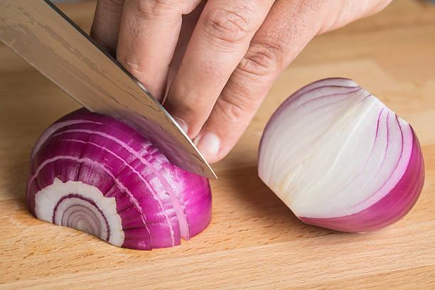chef tagliare a pezzetti di cipolla rossa con un coltello - foto di tropea foto e immagini stock