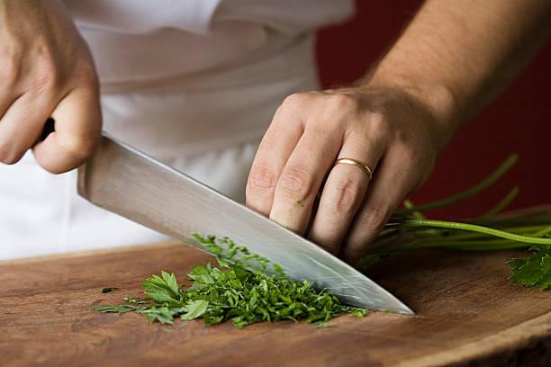 kucharz krojenie pietruszki - ciąć zdjęcia i obrazy z banku zdjęć