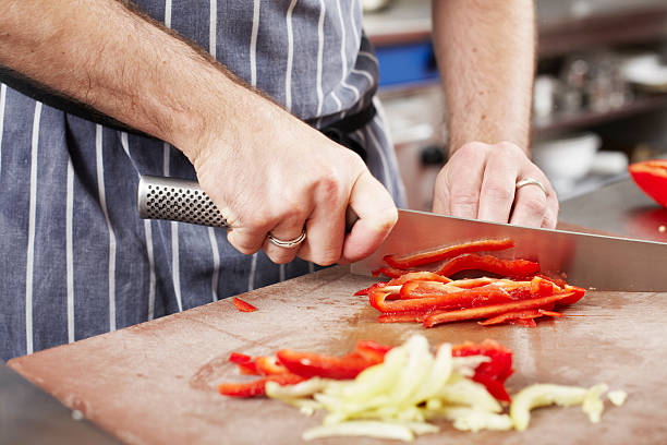 Chef chopping vegetables in kitchen stock photo
