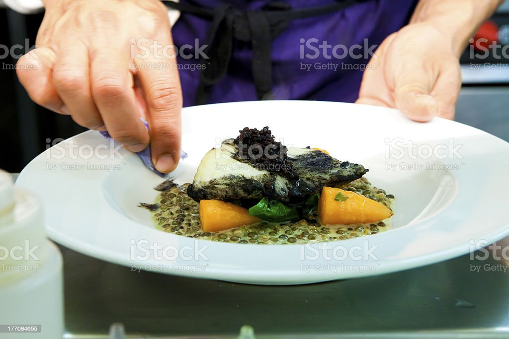 Chef cleaning the side of a dinner plate before serving royalty-free stock photo