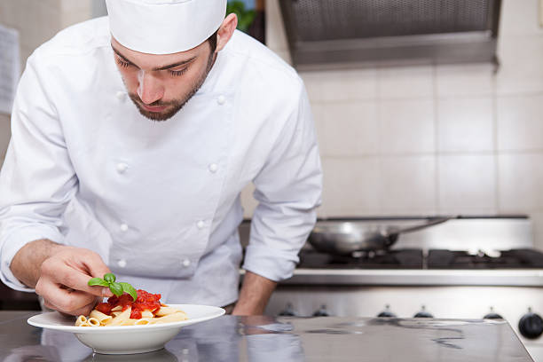 Chef Completing Pasta Male chef completing pasta. chef's whites stock pictures, royalty-free photos & images
