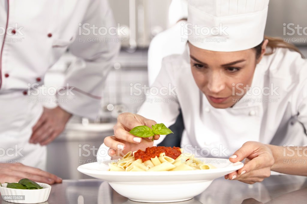 Chef completing pasta with tomato stock photo