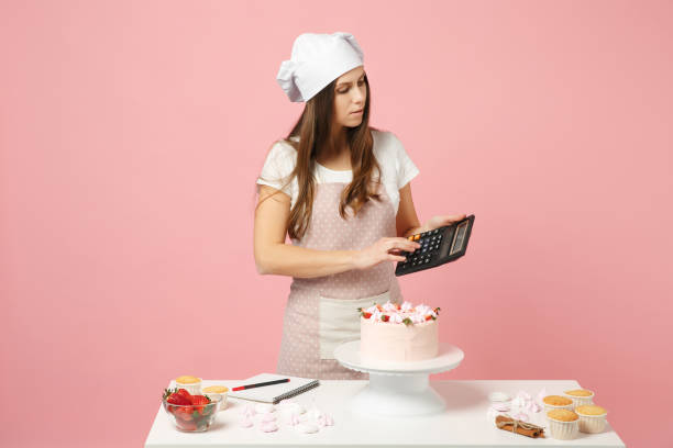 Chef cook confectioner or baker in apron white t-shirt, toque chefs hat cooking cake or cupcake at table hold calculator isolated on pink pastel background in studio. Mock up copy space food concept. stock photo
