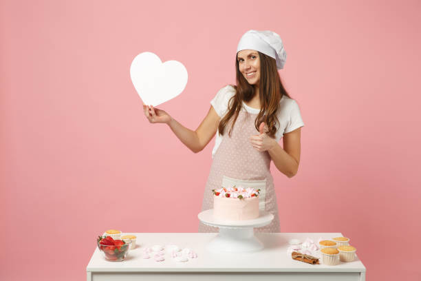 Chef cook confectioner or baker in apron white t-shirt, toque chefs hat cooking cake or cupcake at table hold like heart isolated on pink pastel background in studio. Mock up copy space food concept. stock photo
