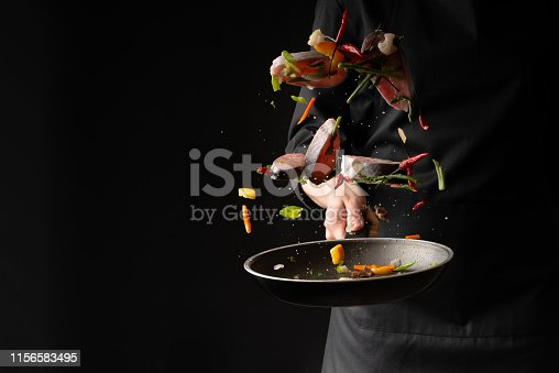 Chef cook fry fish with vegetables on a griddle on a black background. horizontal photo. sea food. healthy food. oriental cuisine, baner