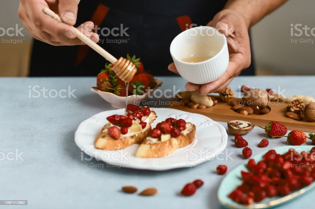 Chef cook prepares Italian bruschetta pours honey with strawberries, cheese, camembert, brie, cooking by chef hand. Authentic lifestyle image stock photo