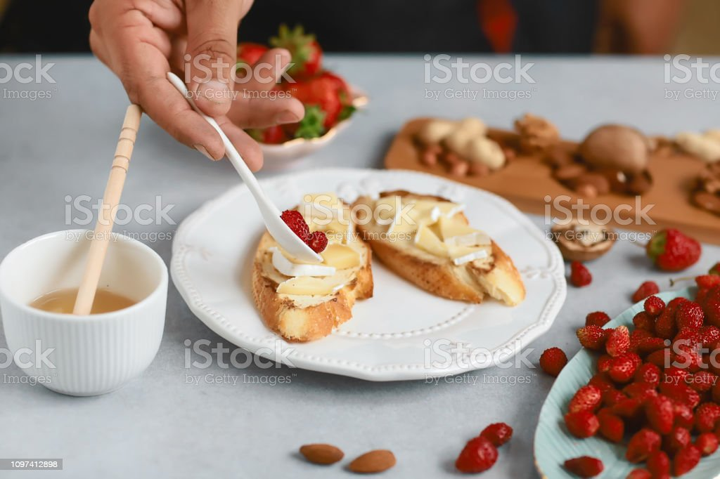 chef cook prepares sweet sandwiches with strawberries, cheese, camembert, brie, nuts and honey on the bruschetta cooking by chef hand on light background. Top view stock photo