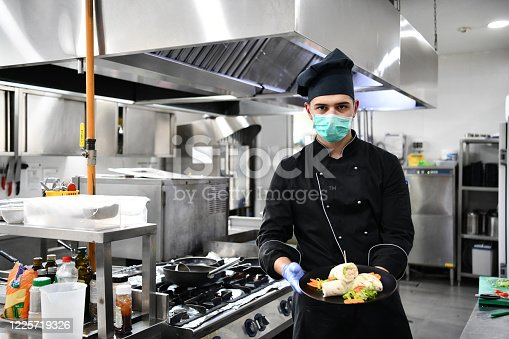 chef cook wearing face protective medical mask for protection from corona virus disease with plate of authentic sandwich at professional restaurant kitchen. Health, safety and pandemic concept in new normal concept