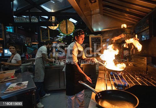 Chef cooking at a restaurant flaming the food - small business concepts