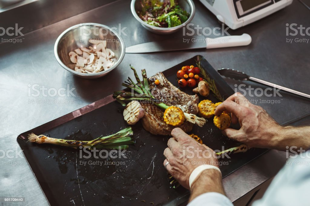 Chef cooking juicy beef steak at restaurant kitchen stock photo