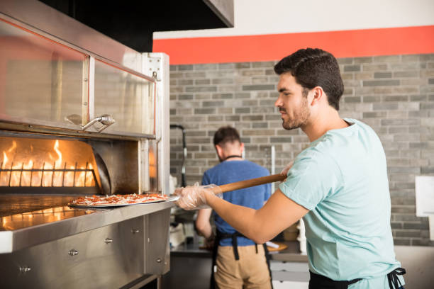 chef cooking pizza and putting it in the oven to bake - pizzeria stock photos and pictures