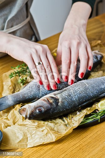 496065234istockphoto Chef cooking sea bass on a wooden table. Black background, side view, space for text. 1136551421