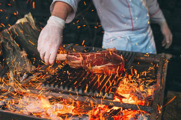 chef gotowanie stek. cook zamienia mięso na ogień. - barbecue zdjęcia i obrazy z banku zdjęć