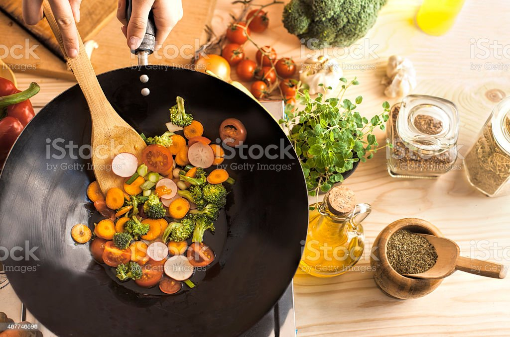Chef cooking vegetables in wok pan stock photo