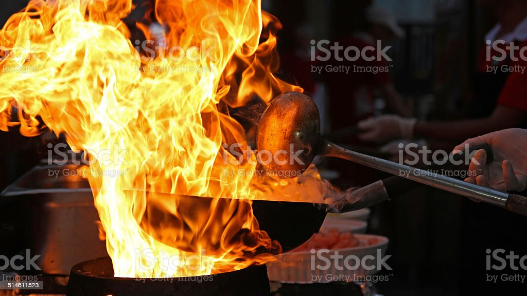 Chef Cooking With Fire In Frying Pan stock photo