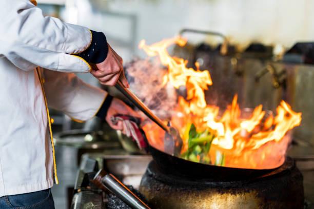 Chef cooking with flame in a frying pan on a kitchen stove Chef in chinese restaurant. chef's whites stock pictures, royalty-free photos & images