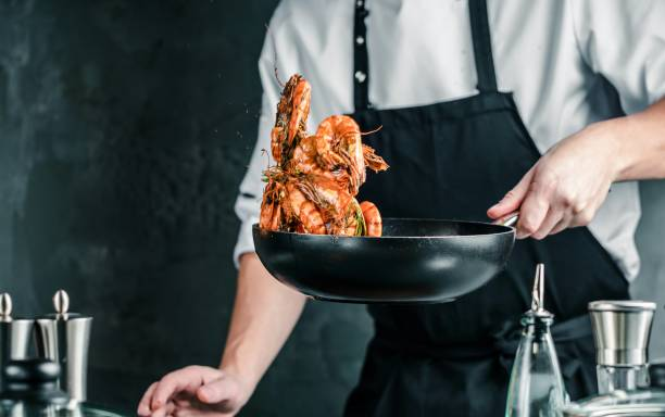 koch kochen mit tiger garnele auf dunklem hintergrund - chefkoch auflauf stock-fotos und bilder
