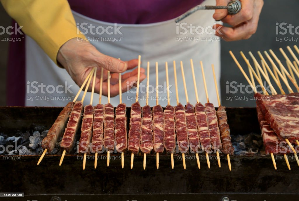 chef cooks Meat called Arrosticini in italian language are a class of traditional italian cuisine of Abruzzo Region - foto stock