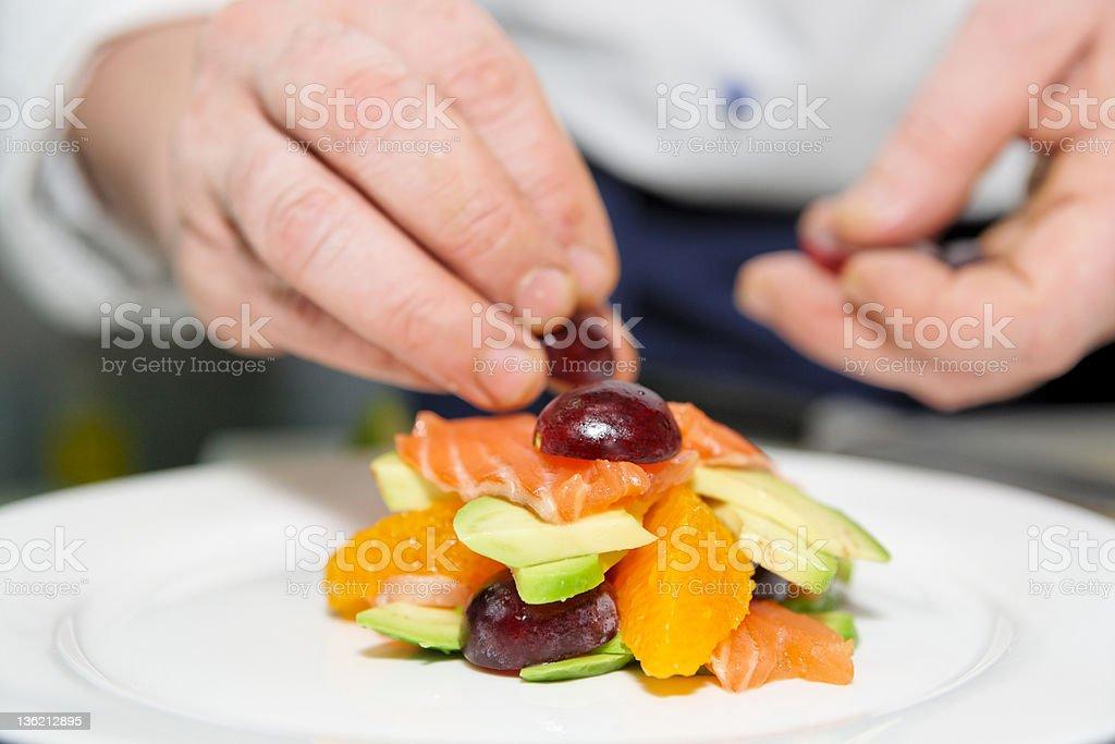 Chef creating a salmon and salad dish royalty-free stock photo