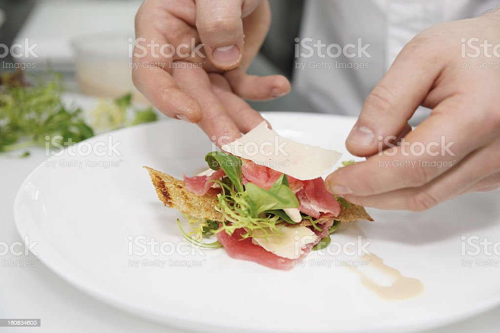 Chef creating gourmet appetizer with salmon, cheese and leaf stock photo