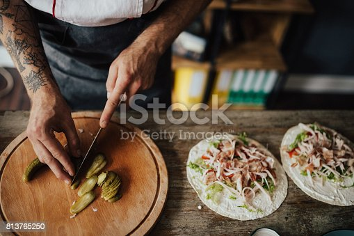 Chef cuts picles in thin slices for wrap sandwich