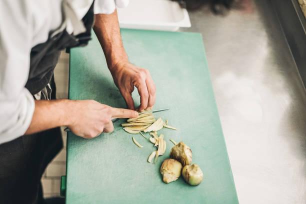 koch schneiden artischocken für abendessen vorbereitung - mann kochen im restaurant küche - fokus auf finger - vegane küche, lifestyle und gesunde ernährung konzept - artischocken gesund stock-fotos und bilder