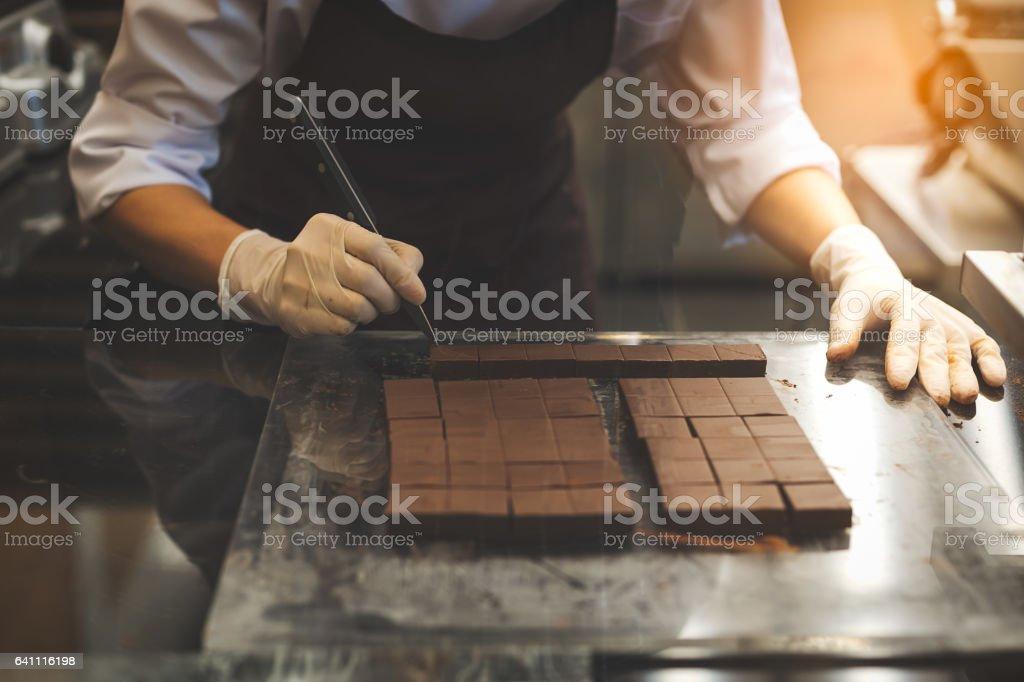 Chef cutting homemade chocolate in kitchen. stock photo