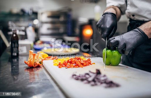 Chef in black latex gloves cutting vegetables in his kitchen in restaurant.