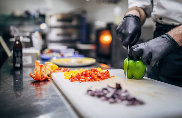 Chef Cutting Paprika Chef in black latex gloves cutting vegetables in his kitchen in restaurant. chef stock pictures, royalty-free photos & images