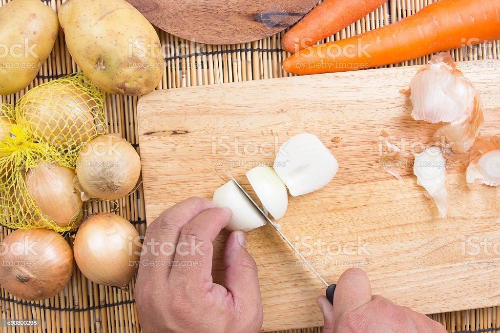 Chef cutting the onion on a wooden board royaltyfri bildbanksbilder