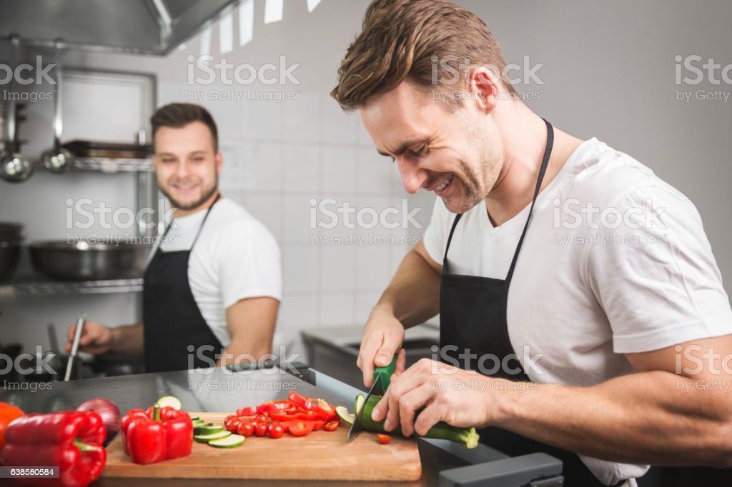 Chef cutting vegetables and his coworker cooking stock photo