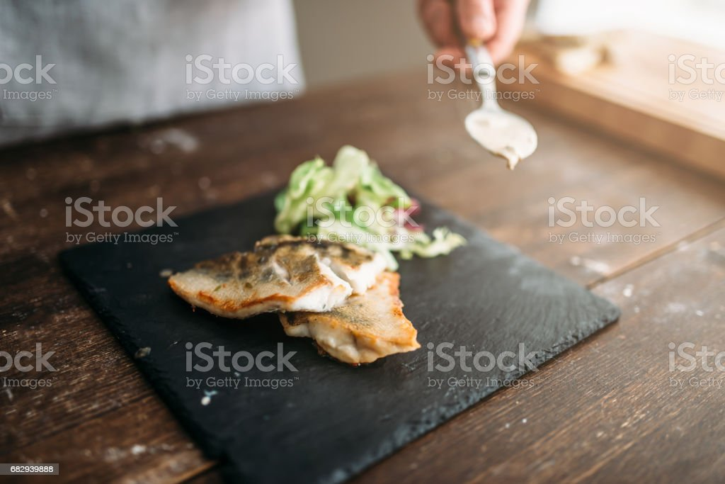 Chef decorate with vegetables dish of fried fish royalty-free stock photo