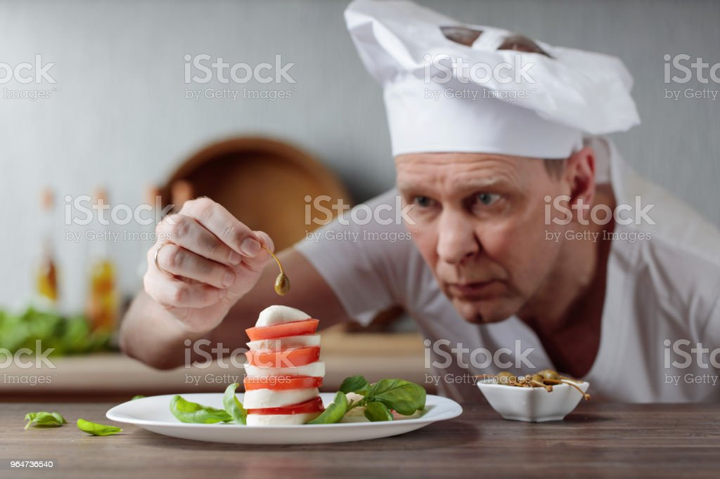 Chef decorates snacks with mozzarella and capers . royalty-free stock photo