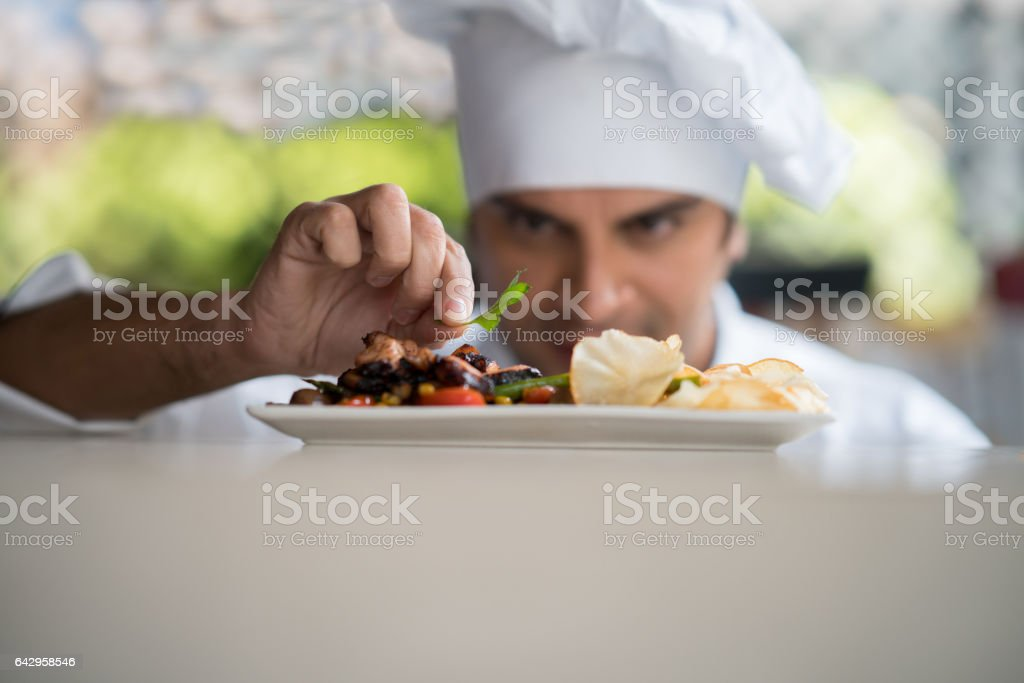 Chef decorating a plate at a restaurant stock photo