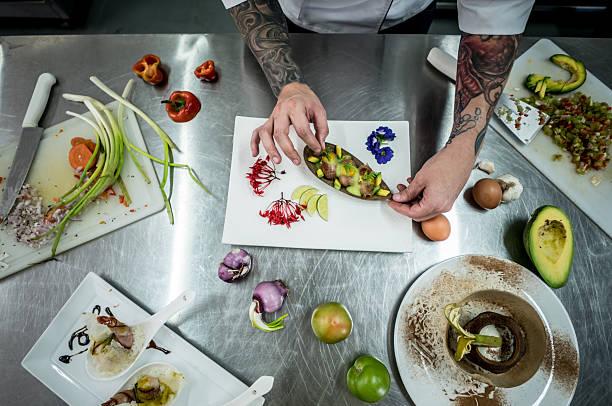 chef decorating a plate - essen tattoos stock-fotos und bilder