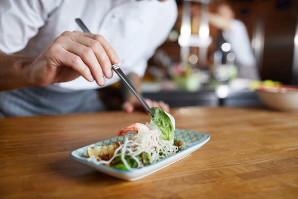 küchenchef decorating gourmet dish closeup - kochkunst stock-fotos und bilder