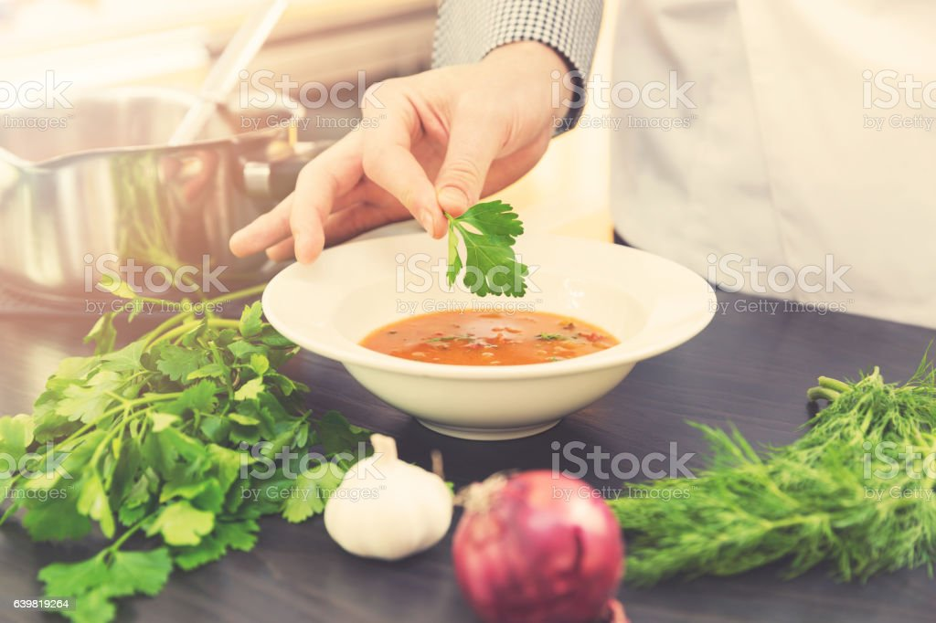 chef decorating soup with herbs in kitchen stock photo