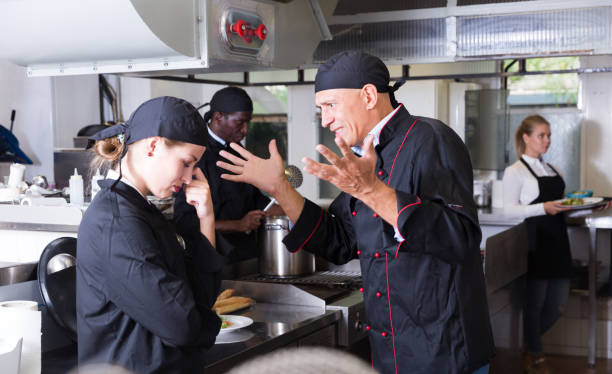 chef dissatisfied with work of girl - chef triste foto e immagini stock