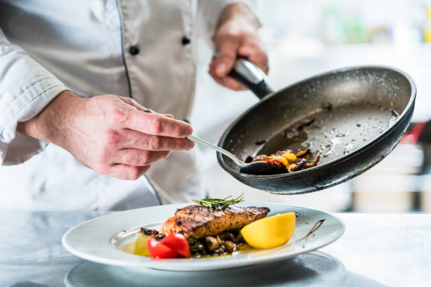 Chef finishing food in his restaurant kitchen stock photo