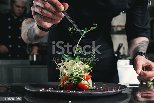 Chef finishing healthy salad on a black plate with tweezers. almost ready to serve it on a table.