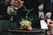 ピンセットで黒のプレートに健康的なサラダを仕上げるシェフ。テーブルの上にそれを提供するほぼ準備ができて